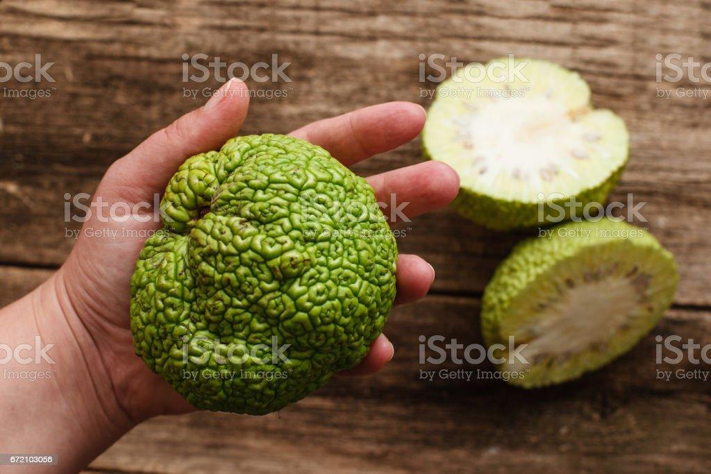 Woman showing green tropical fruit flat lay stock photo
