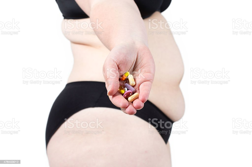 Woman showing her fat body and holding a tablets. stock photo