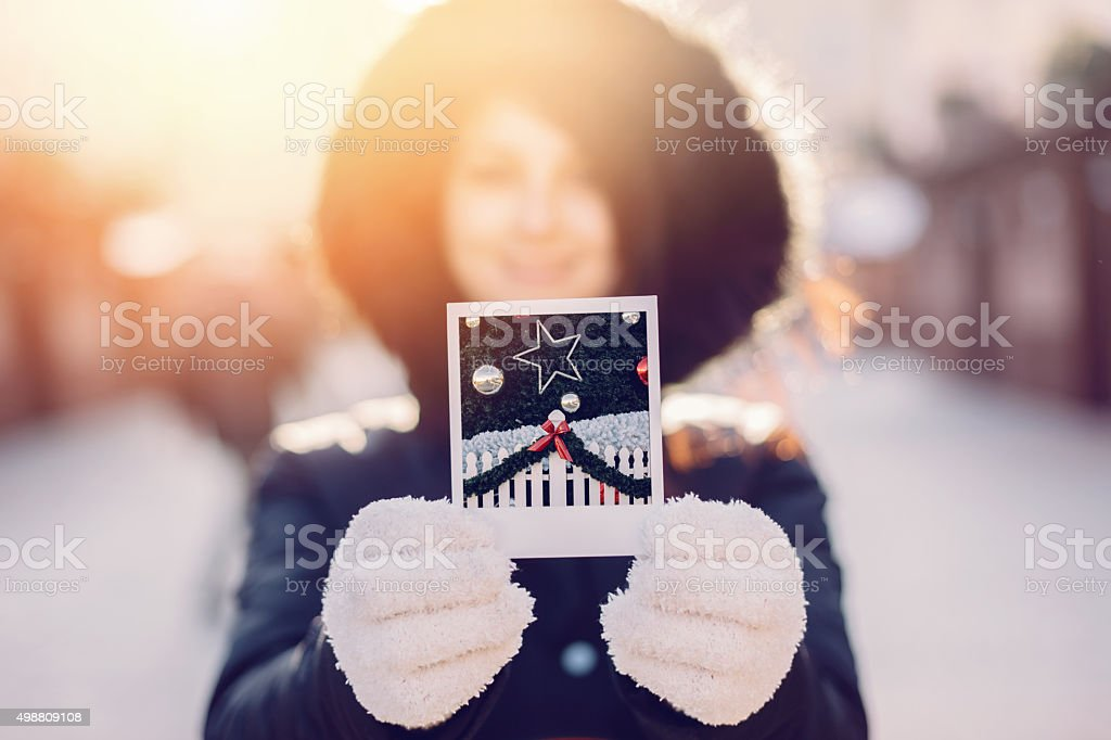 Woman showing instant photo of Christmas tree stock photo