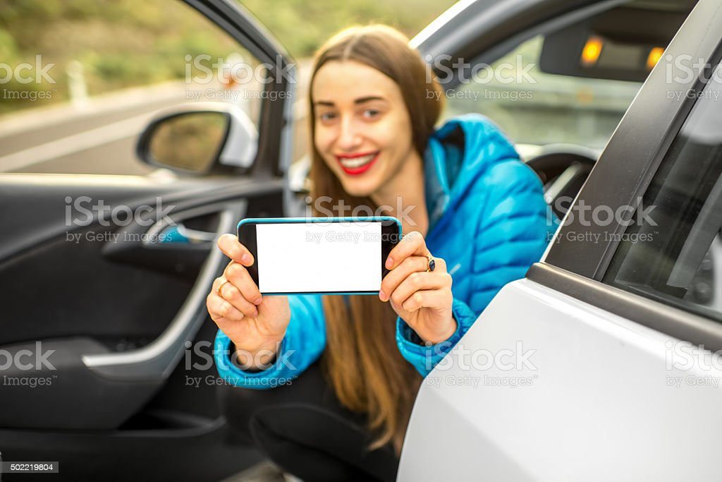 Woman showing phone sitting in the car stock photo