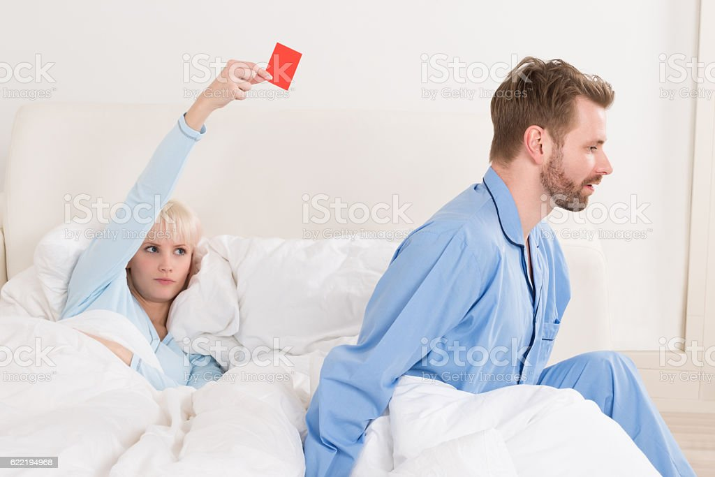 Woman Showing Red Card To Man In Bed stock photo