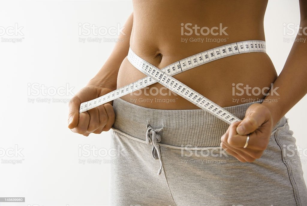 Woman showing she has lost inches off her waist stock photo