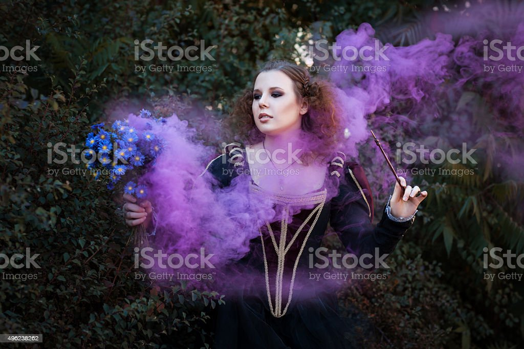 Woman showing tricks with a magic wand. stock photo