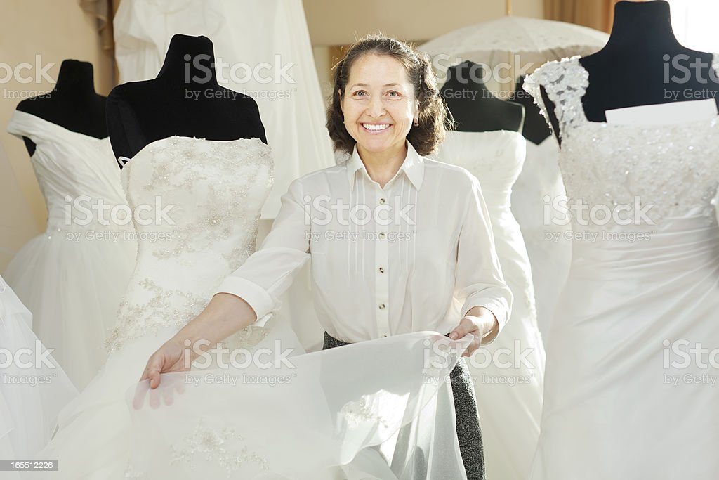 Woman shows bridal gown at shop royalty-free stock photo