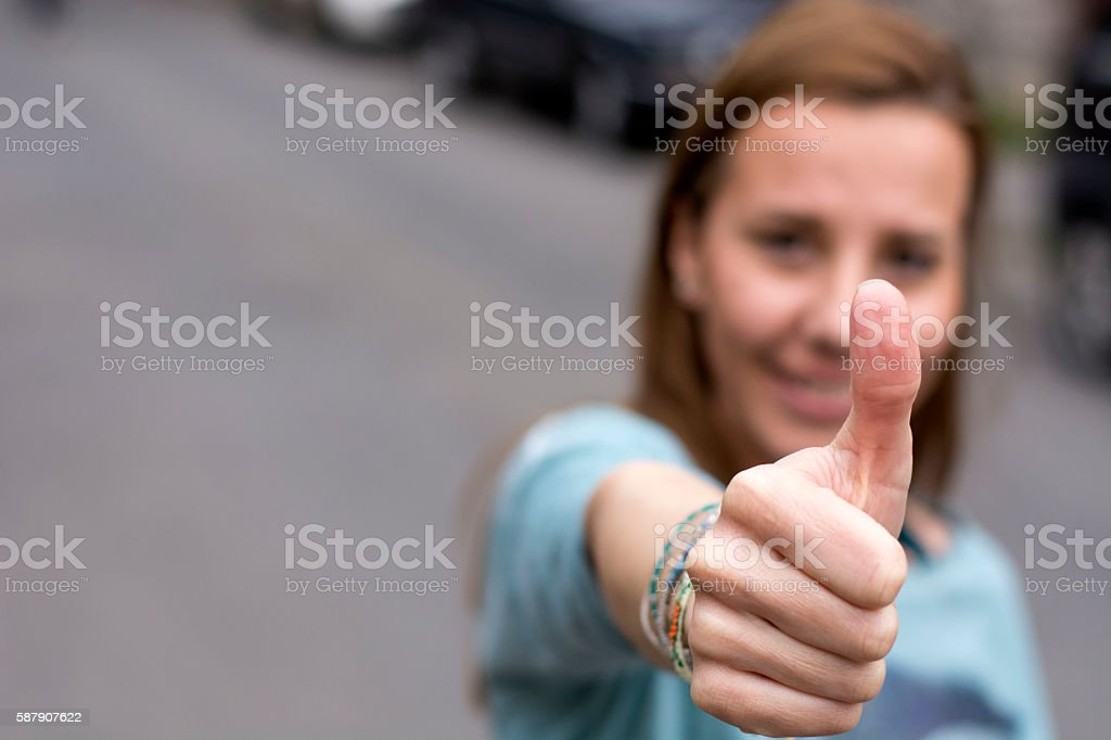 Woman shows thumb up sign stock photo