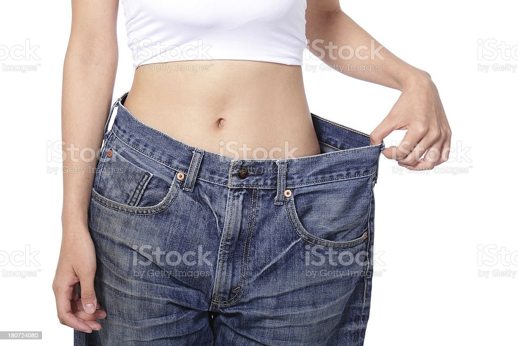 woman shows weight loss by wearing old jeans royalty-free stock photo
