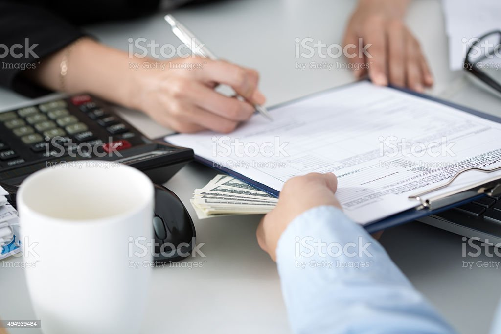 Woman signing documents for a batch of hundred dollar bills stock photo