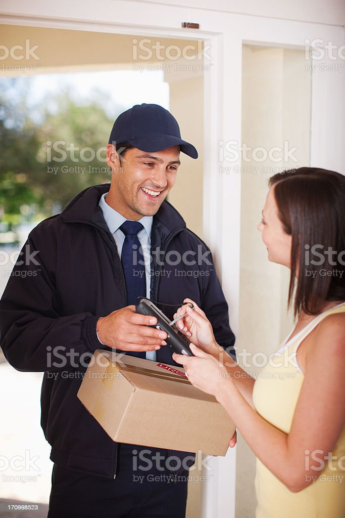 Woman signing for box from delivery man stock photo