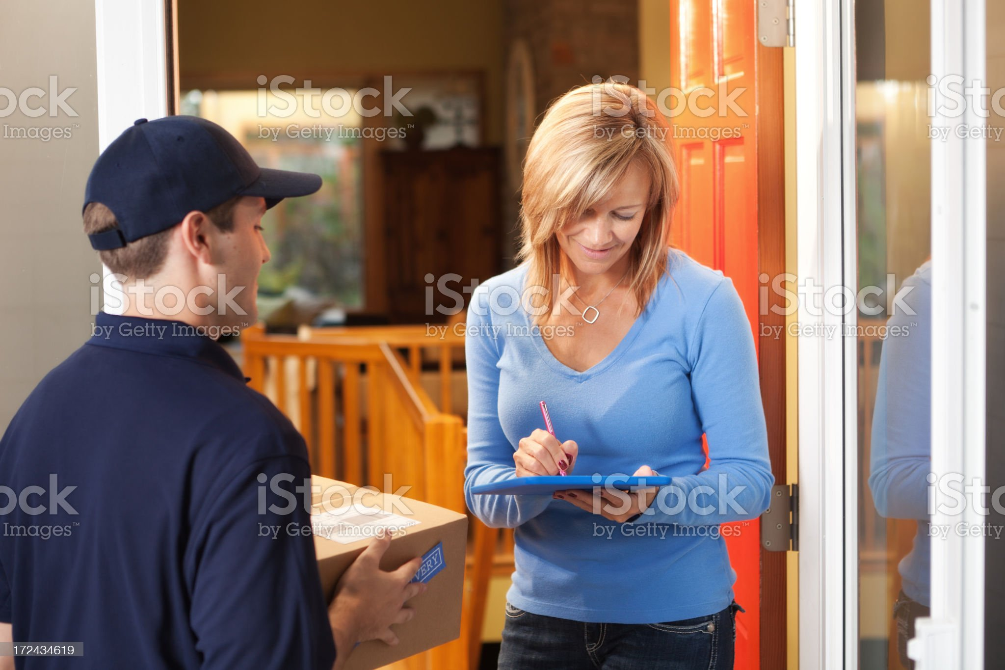 Woman Signing for Package Delivered by Delivery Person to House royalty-free stock photo