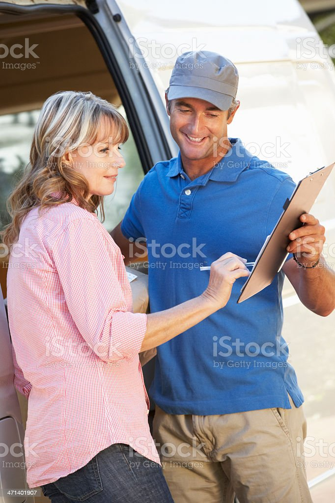 Woman Signing For Packager Delivered By Courier royalty-free stock photo