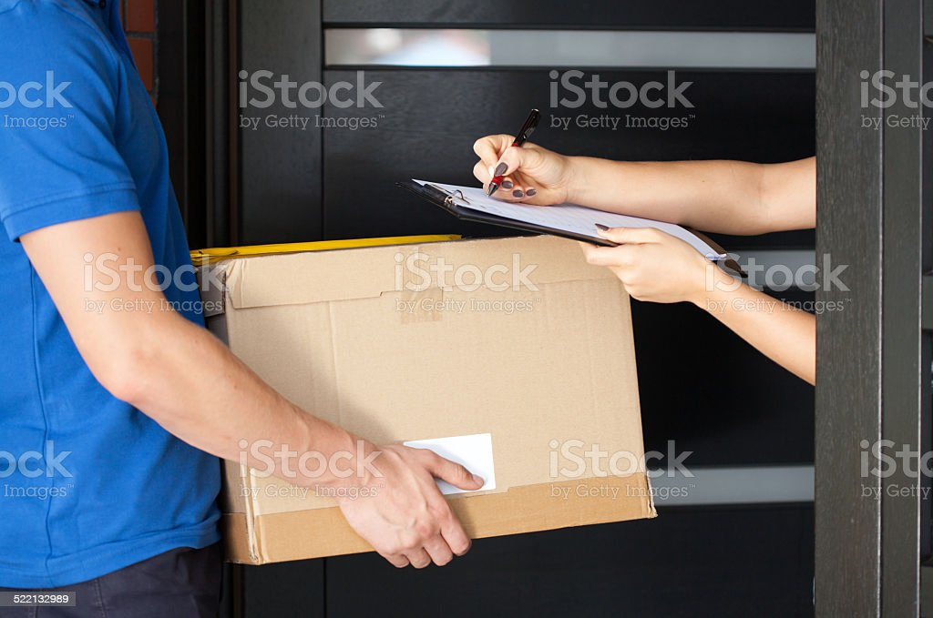 Woman signing parcel delivery papers stock photo