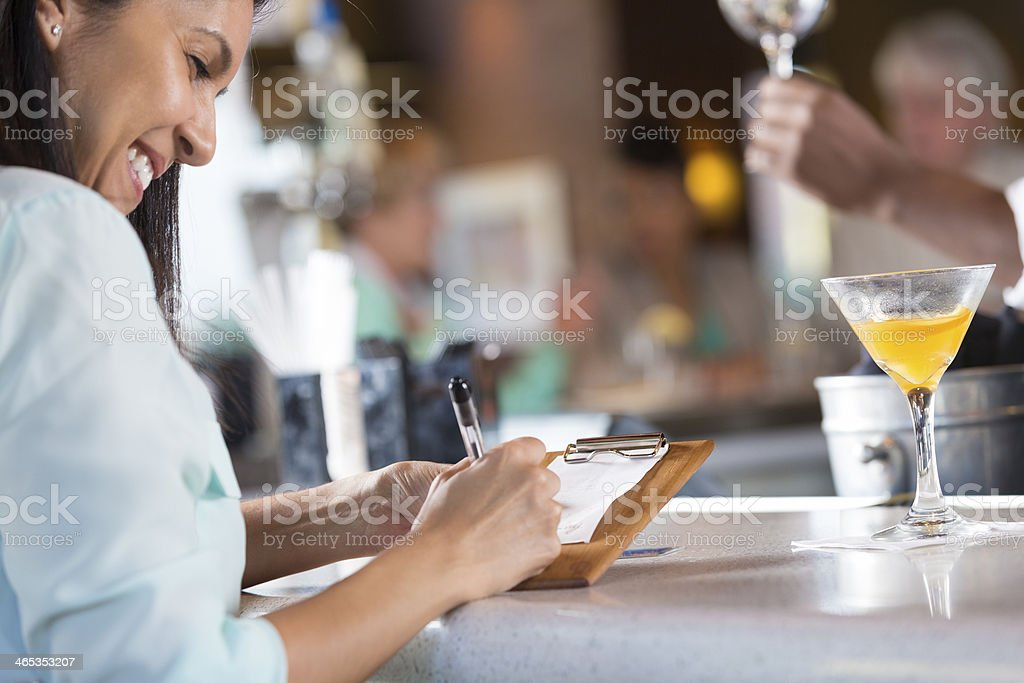 Woman signing receipt after paying bar tab in restaurant stock photo