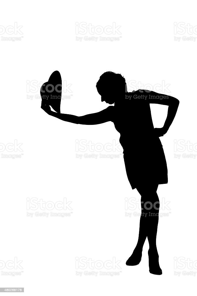 woman silhouette taking off a hat stock photo