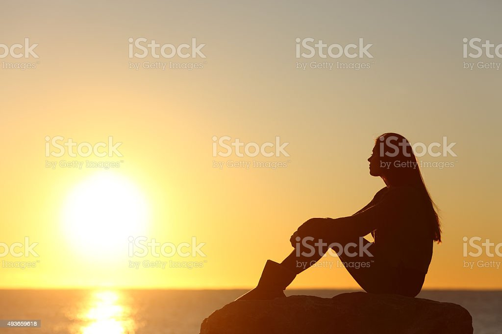 Woman silhouette watching sun in a sunset stock photo