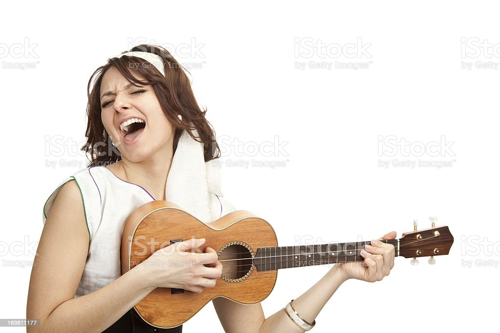 A woman singing and playing a ukulele against a white back stock photo