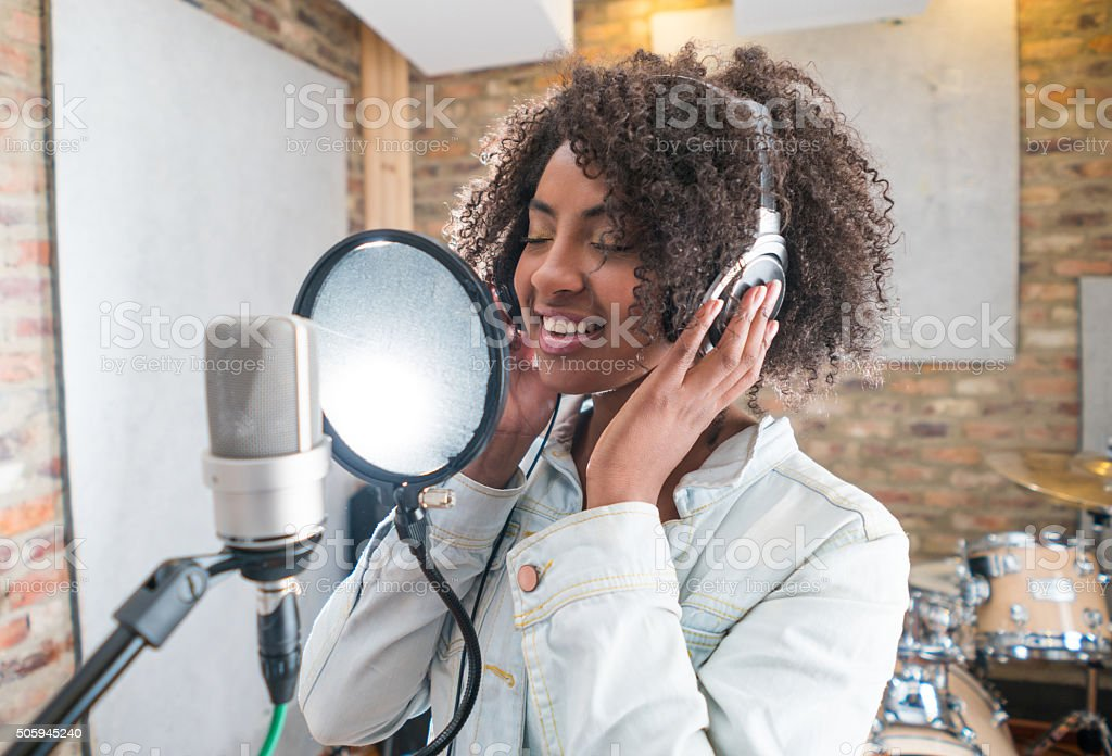 Woman singing at a recording studio stock photo