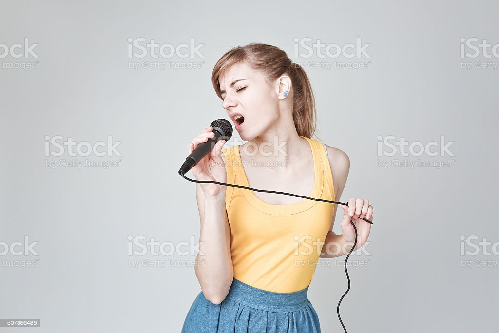 woman singing into a microphone stock photo