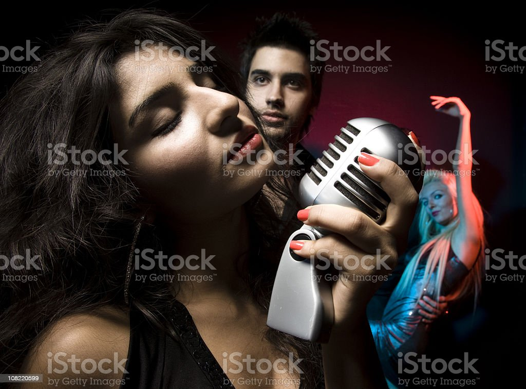 Woman Singing into Microphone with People Watching and Dancing stock photo