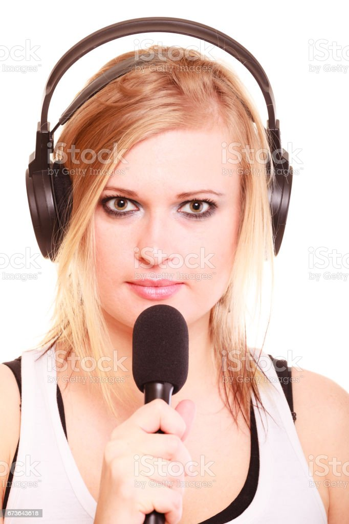 Woman singing to microphone wearing headphones stock photo