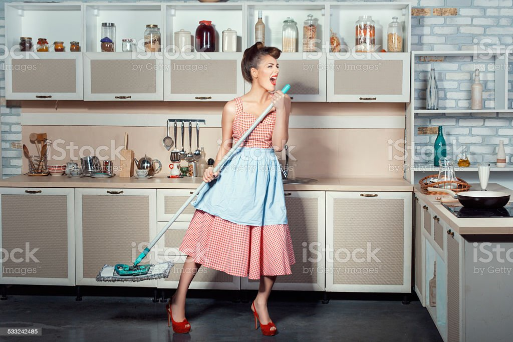 Woman sings and cleans the house. stock photo