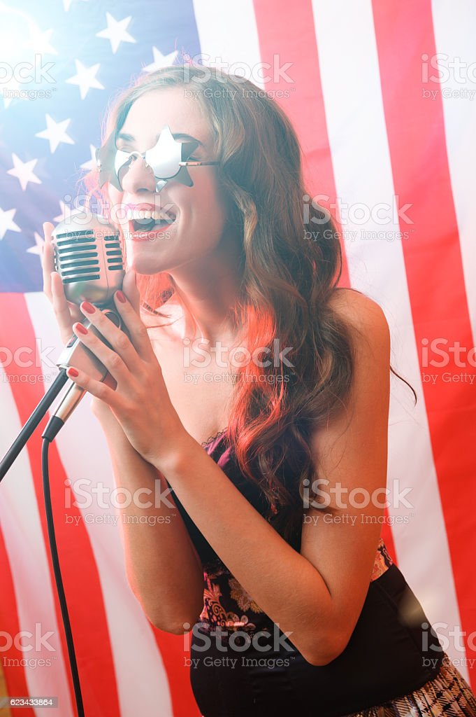 Woman Sings on a Background of the American Flag stock photo