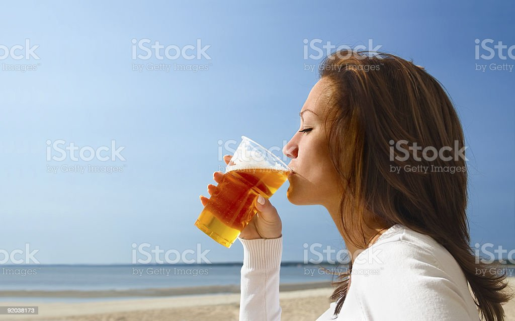 Woman sipping beach on a cool beach royalty-free stock photo