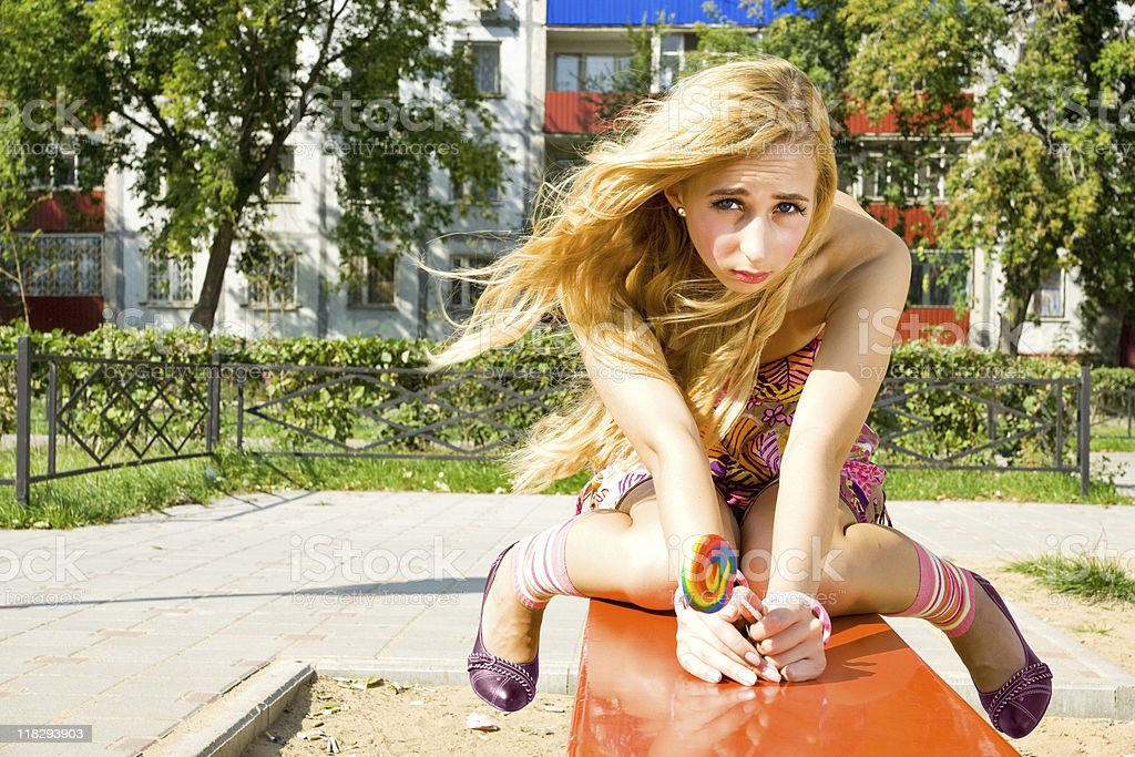 Woman siting on bench with lollipop royalty-free stock photo