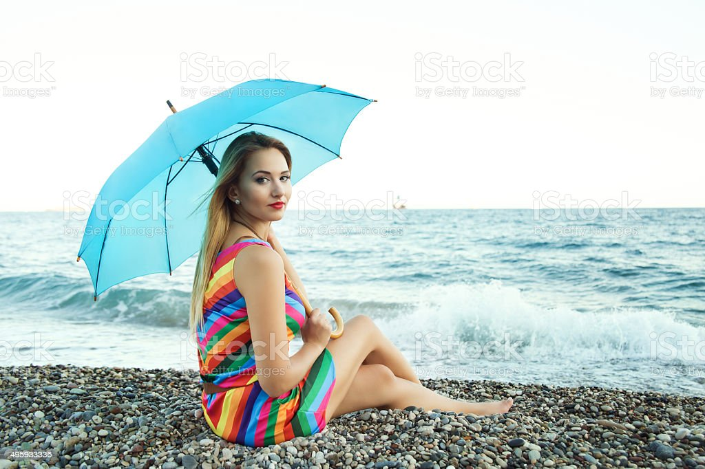 Woman siting with parasol by the sea stock photo