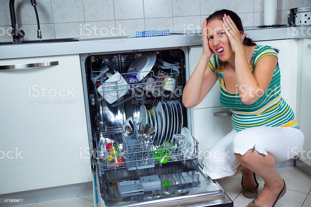 Woman sits near to the open dishwasher on kitchen royalty-free stock photo