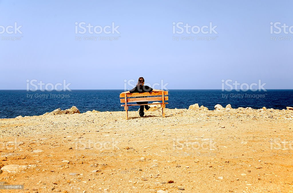 Woman sits on a bench at coast royalty-free stock photo