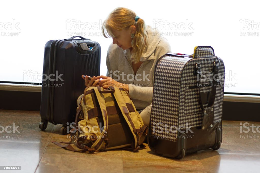 Woman Sits on Aiport Floor Reading Phone, Surrounded by Luggage stock photo