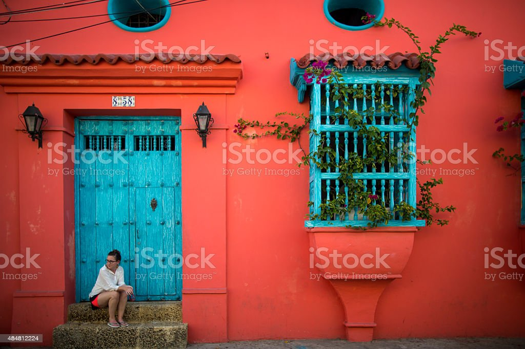 Woman sits on door step in Cartagena, Colombia stock photo