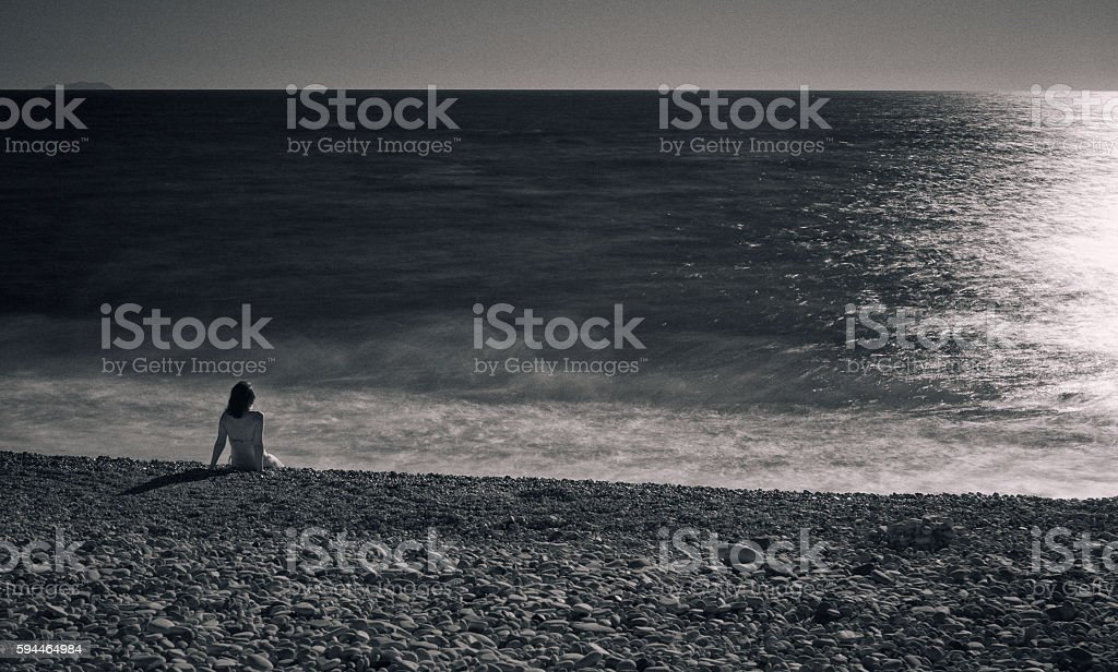 Woman sits on the beach at the sunset stock photo