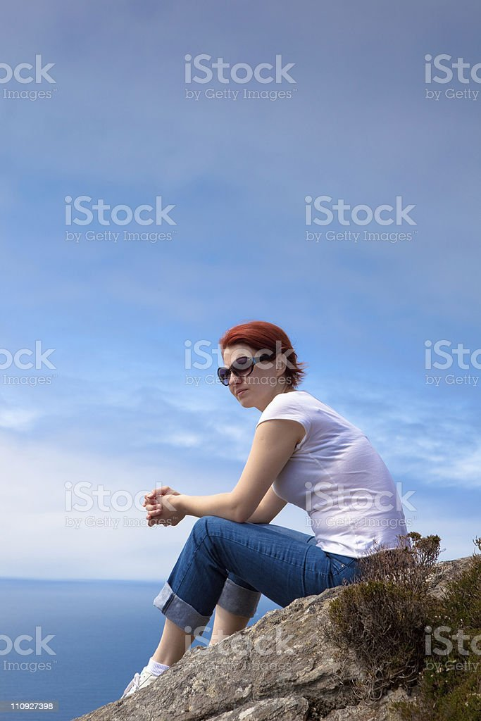 Woman sits on top of mountain royalty-free stock photo