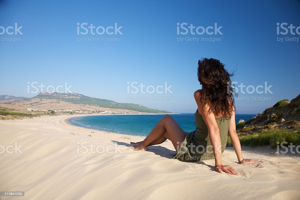 woman sits over Bolonia beach stock photo