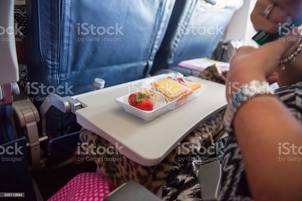 Woman sits with purchased airplane food on tray in airplane stock photo