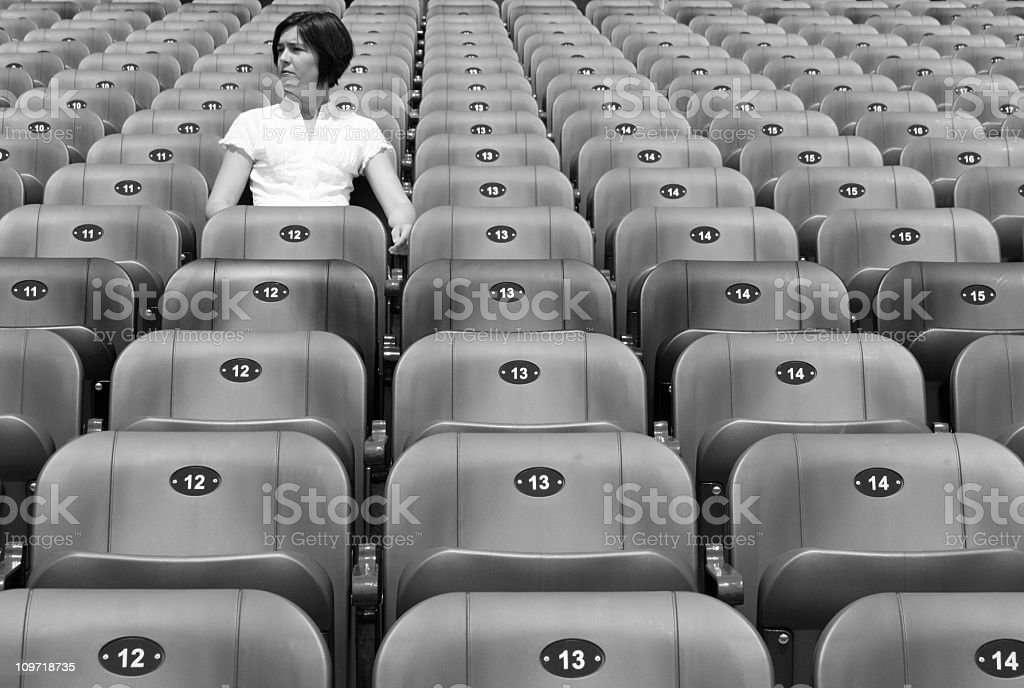 Woman Sitting Alone in Stadium Chairs, Black and White stock photo