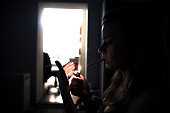 Woman sitting alone in the dark and lighting cigarette