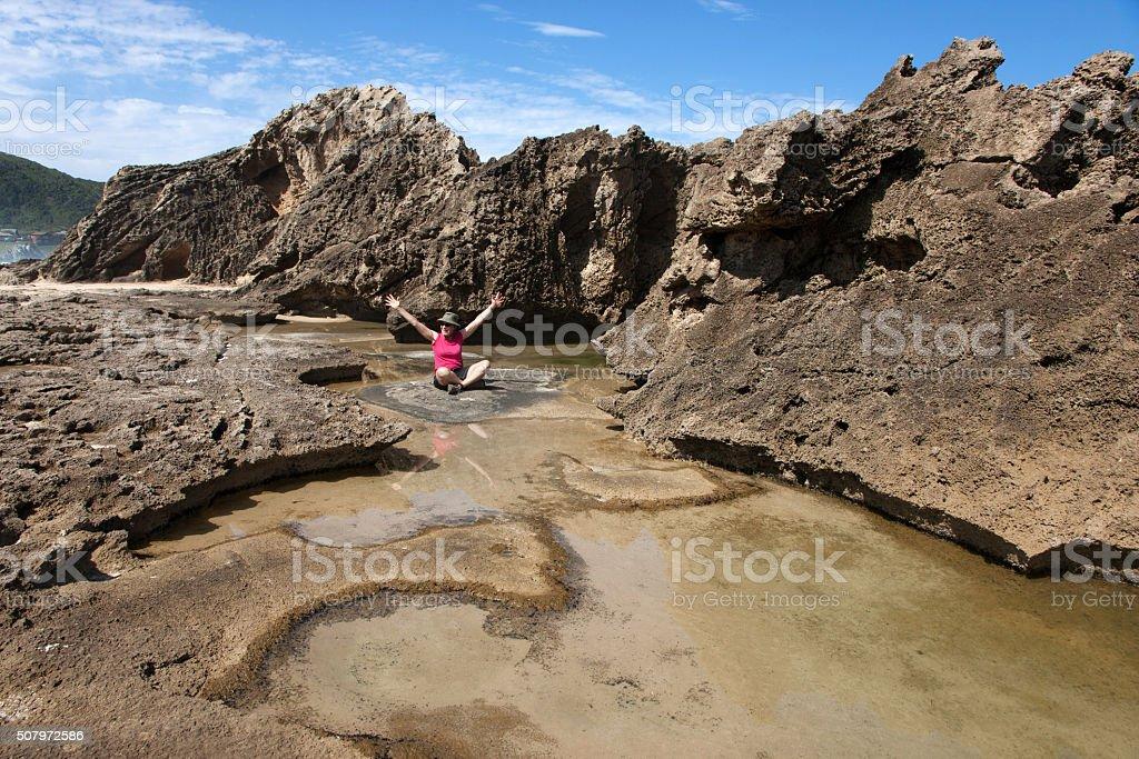 Woman sitting among petrified dune rocks in South Africa 2 stock photo