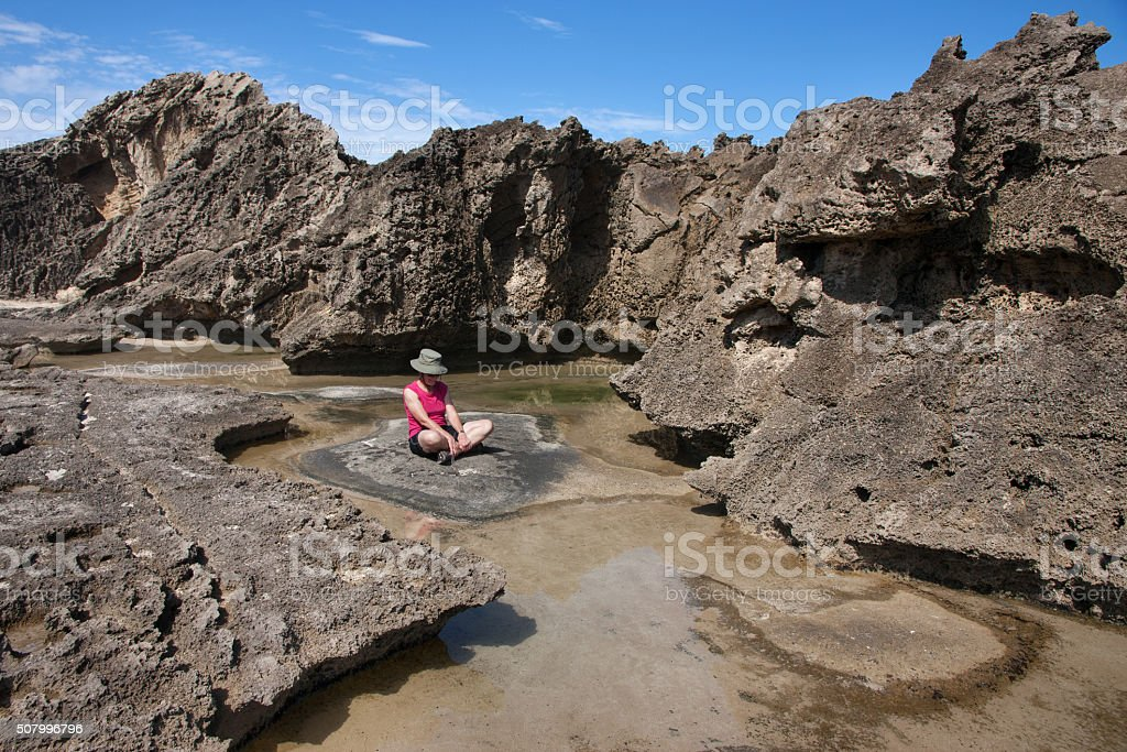 Woman sitting among petrified dune rocks in South Africa 3 stock photo