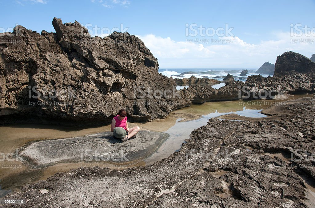 Woman sitting among petrified dune rocks in South Africa 4 stock photo