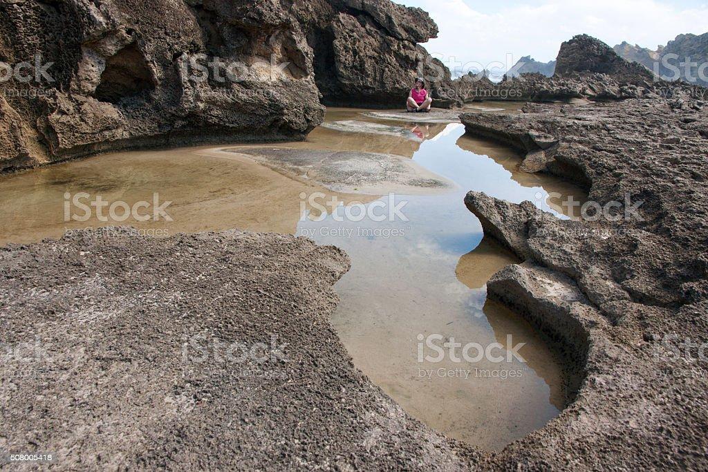 Woman sitting among petrified dune rocks in South Africa 5 stock photo