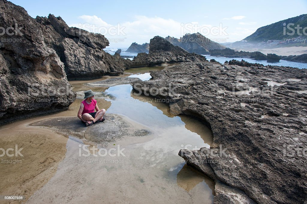 Woman sitting among petrified dune rocks in South Africa 6 stock photo