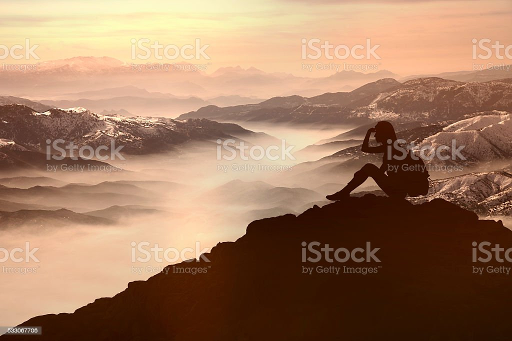 Woman sitting and look ahead on mountain stock photo