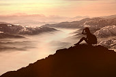Woman sitting and look ahead on mountain