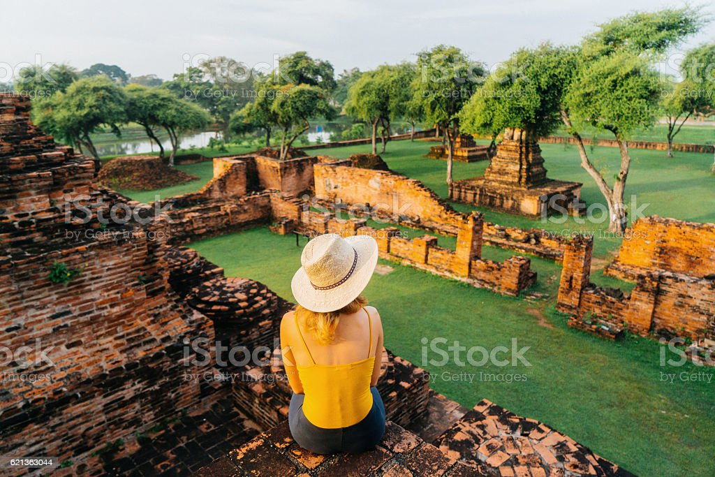 Woman sitting and looking at ancient Buddhist Temple stock photo