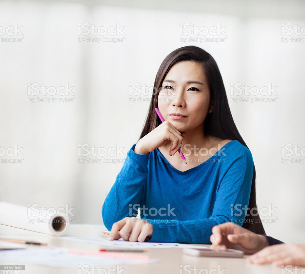Woman sitting and thinking in design studio office stock photo