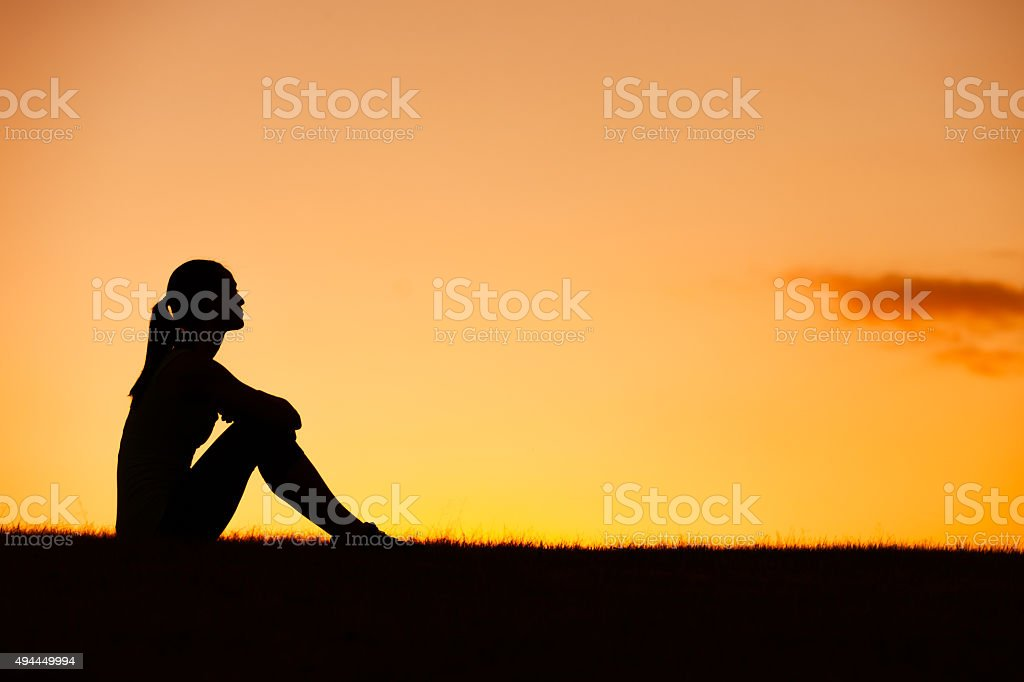 Woman sitting and watching a sunset stock photo