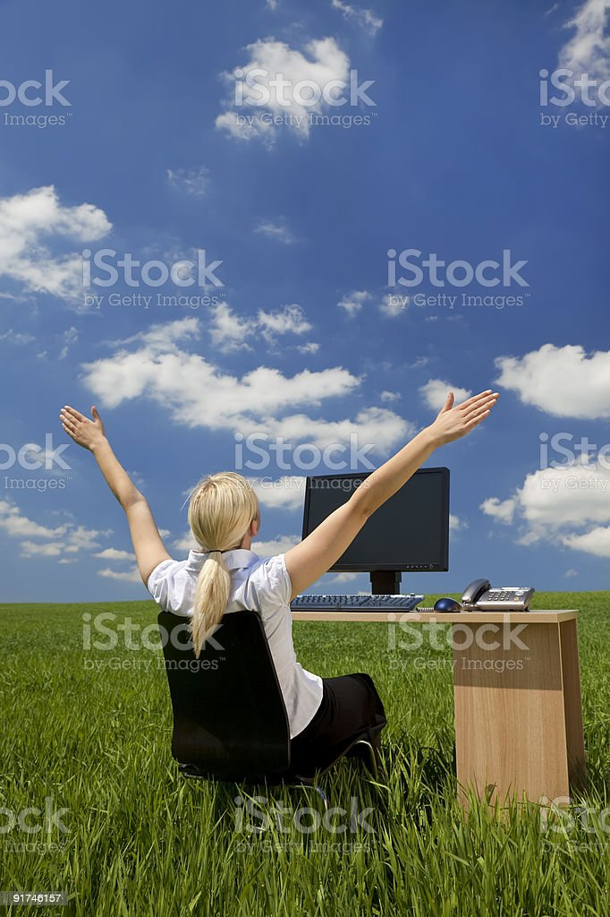 Woman sitting at a computer in a green field royalty-free stock photo