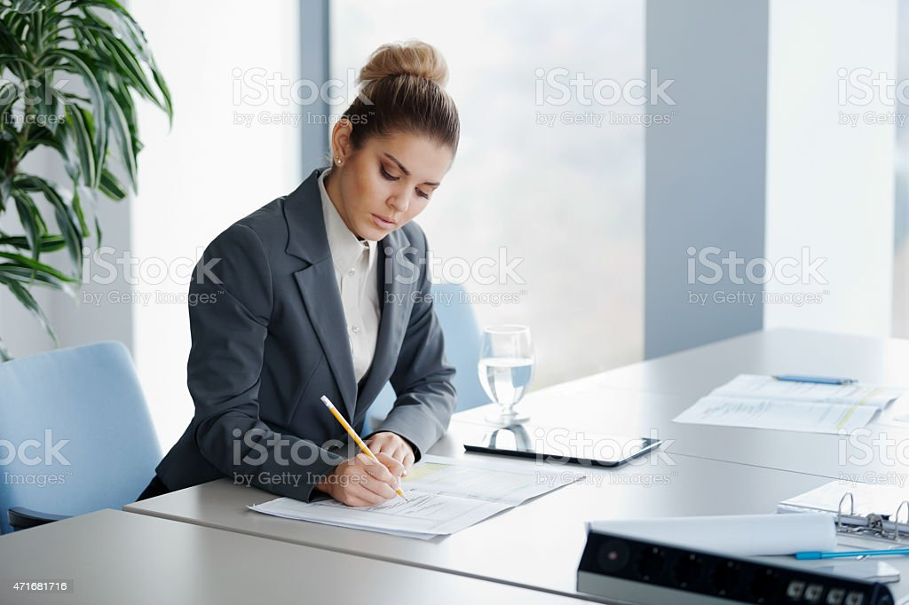 A woman sitting at a large table taking notes with a pencil  stock photo